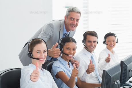 Colleagues with headsets using computers while gesturing thumbs upの素材 [FYI00007490]