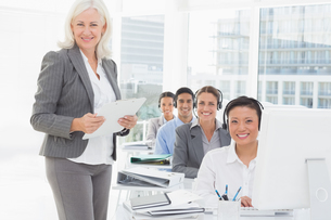 Smiling businesswoman looking at camera while work team using computerの素材 [FYI00007512]