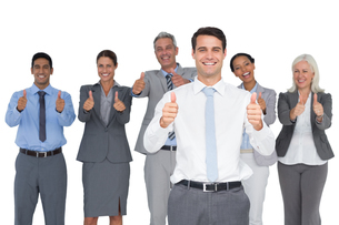 Happy business people looking at camera with thumbs upの素材 [FYI00007524]