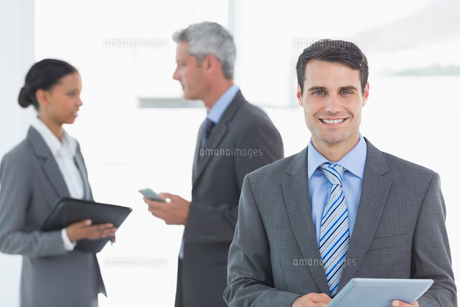 Businessman using a tablet  with colleagues behind in officeの写真素材 [FYI00007565]