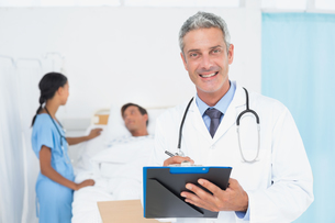Doctor with colleagues and patient behindの写真素材 [FYI00007608]