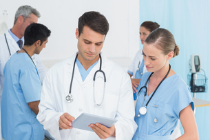 Report reading with colleagues and patient behindの写真素材 [FYI00007618]