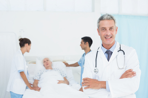 Doctor with colleagues and patient behindの写真素材 [FYI00007626]