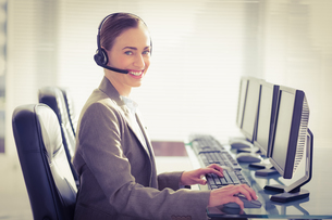 Smiling businesswoman with headset using computersの写真素材 [FYI00007633]