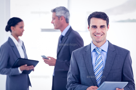 Businessman using a tablet  with colleagues behind in officeの写真素材 [FYI00007647]