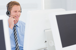 Handsome agent with headset typing on keyboardの写真素材 [FYI00007686]