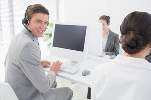 Smiling businessman wearing headsetの写真素材 [FYI00007722]