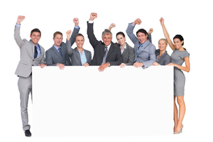 Excited business team holding posterの写真素材 [FYI00007734]