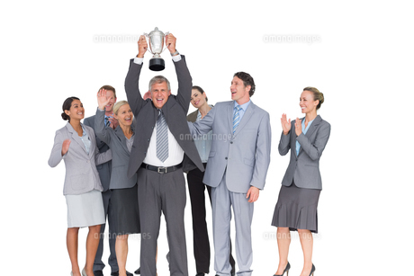 Excited business team cheering at camera with trophyの写真素材 [FYI00007737]