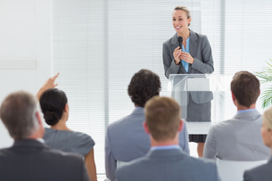 Pretty businesswoman talking in microphone during conferenceの素材 [FYI00007745]