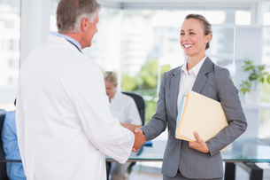 Confident doctor greeting pretty businesswomanの写真素材 [FYI00007772]