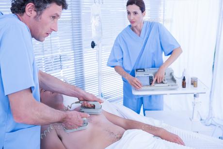 Medical team resuscitating a man with a defibrillatorの写真素材 [FYI00007773]