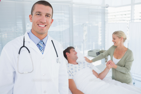 Smiling doctor looking at camera with his patient behindの写真素材 [FYI00007787]