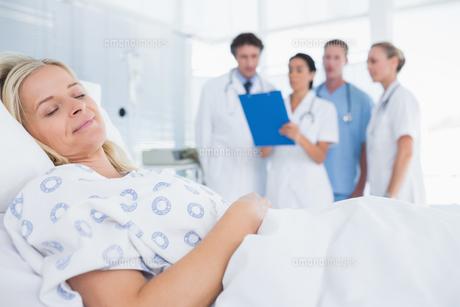 Sleeping patient with doctors behindの写真素材 [FYI00007793]