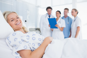 Smiling patient looking at camera with doctors behindの写真素材 [FYI00007796]
