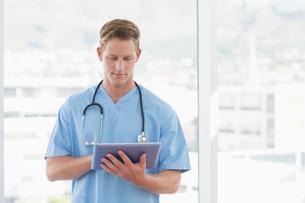 Doctor writing on clipboard beside windowsの写真素材 [FYI00007801]
