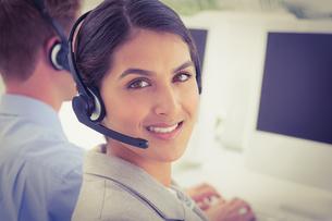 Smiling businesswoman wearing headsetの写真素材 [FYI00007819]