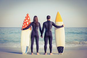 Couple in wetsuits with surfboard on a sunny dayの写真素材 [FYI00007846]