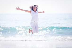 Carefree woman jumping on the beachの写真素材 [FYI00007860]
