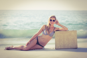 Stylish blonde leaning on suitcase on the beachの写真素材 [FYI00007871]