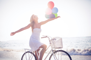 Beautiful blonde on bike ride holding balloonsの写真素材 [FYI00007874]