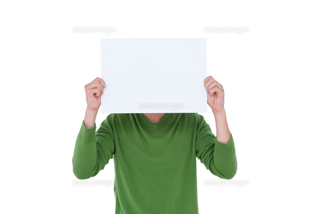 Casual man hiding his head with blank paperの写真素材 [FYI00007897]