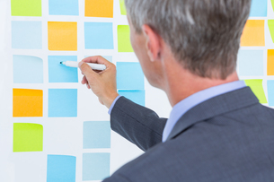 Puzzled businessman looking post its on the wallの写真素材 [FYI00007907]