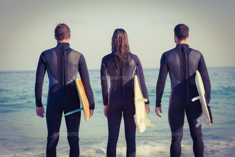 Friends on wetsuits with a surfboard on a sunny dayの写真素材 [FYI00007913]