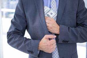 Dodgy businessman with dollar billsの写真素材 [FYI00007918]
