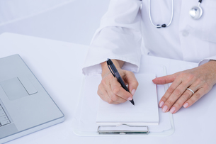 Doctor writing on a notepadの写真素材 [FYI00007931]