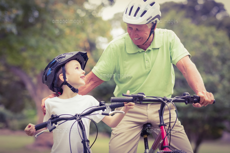 Happy grandfather with his granddaughter on their bikeの写真素材 [FYI00007947]