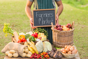 Farmer standing at his stall and holding chalkboardの写真素材 [FYI00007963]