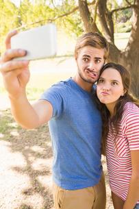 Cute couple doing selfie in the parkの写真素材 [FYI00007964]
