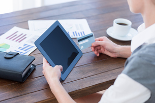 Businesswoman using tablet pc and holding credit cardの写真素材 [FYI00007984]