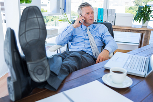 Businessman relaxing in a swivel chair and having a phone callの写真素材 [FYI00007988]