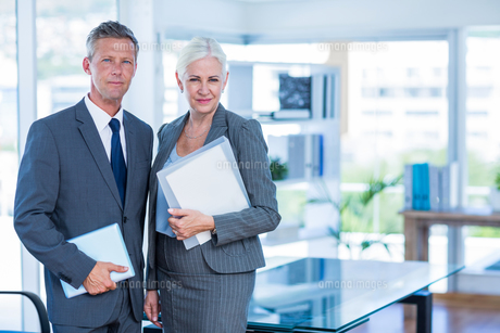Happy business people looking at camera and holding shieldの写真素材 [FYI00008033]