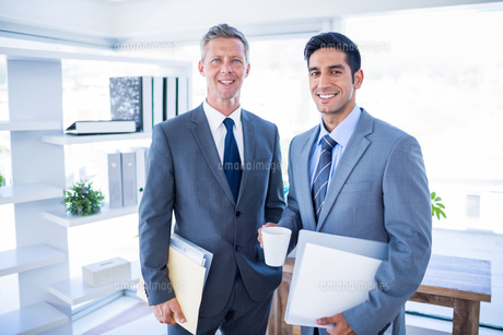 Happy businessman looking at camera and holding filesの写真素材 [FYI00008034]