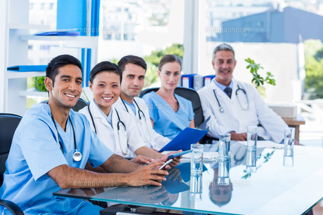 Happy doctors looking at camera while sitting at a tableの写真素材 [FYI00008078]