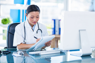 Concentrated doctor writing on clipboardの写真素材 [FYI00008080]