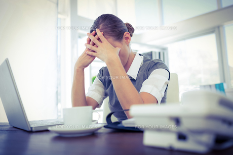 Depressed businesswoman with hands on headの素材 [FYI00008091]