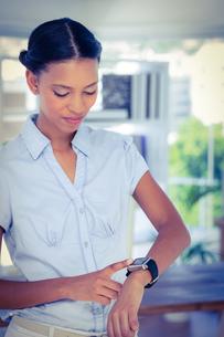 Serious businesswoman using her smart watchの写真素材 [FYI00008095]