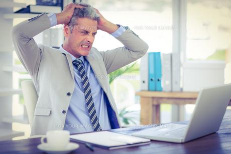 Furious businessman looking at laptop computerの写真素材 [FYI00008096]