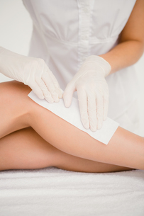 Therapist waxing womans leg at spa centerの写真素材 [FYI00008231]