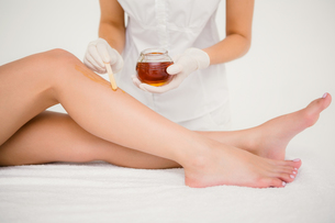 Therapist waxing womans leg at spa centerの写真素材 [FYI00008232]
