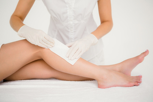 Therapist waxing womans leg at spa centerの写真素材 [FYI00008234]