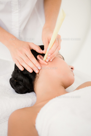 Beautiful woman receiving ear candle treatment at spa centerの素材 [FYI00008236]