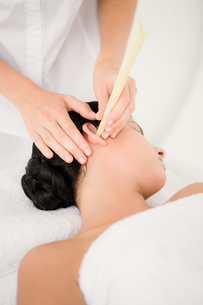 Beautiful woman receiving ear candle treatment at spa centerの写真素材 [FYI00008236]