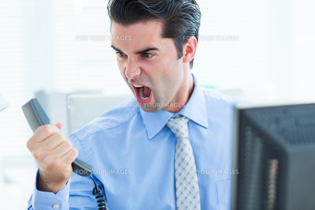 Businessman shouting as he holds out phone at officeの写真素材 [FYI00008262]
