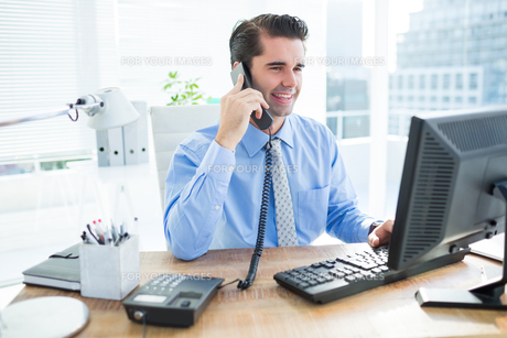 Smiling businessman using his computer ans phoningの写真素材 [FYI00008265]
