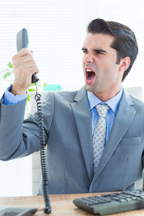 Businessman shouting as he holds out phone at officeの写真素材 [FYI00008273]